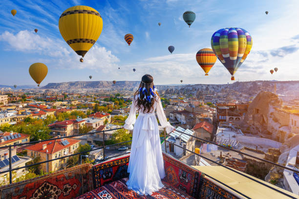 Beautiful girl standing on the hotel and looking to hot air balloons in Cappadocia, Turkey. stock photo
