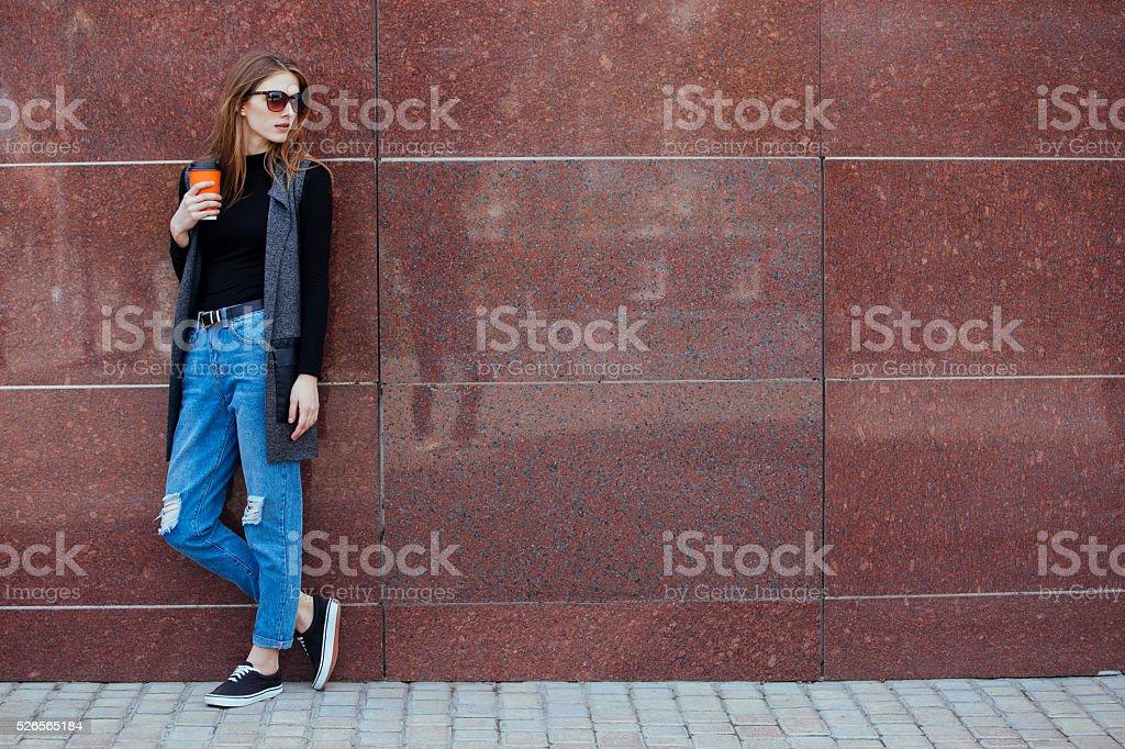Красивая девушка стоит против стены с кофе. стоковое фото