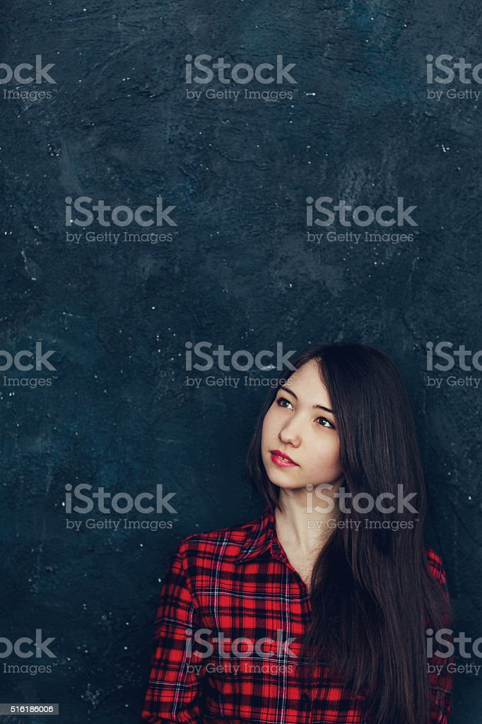 beautiful girl stands near the wall in the Studio stock photo