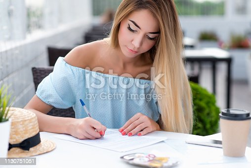 istock Beautiful girl summer cafe. Fills contract writing, legal contract for services. Drawing up paper legally correct certified document. Woman long hair dress. Business lady working veranda restaurant. 1130751051