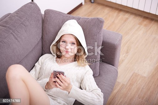 istock beautiful girl talking and typing to mobile on sofa 522474765