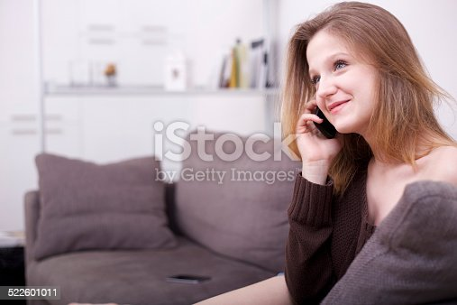 istock beautiful girl talking and typing to mobile on sofa 522601011