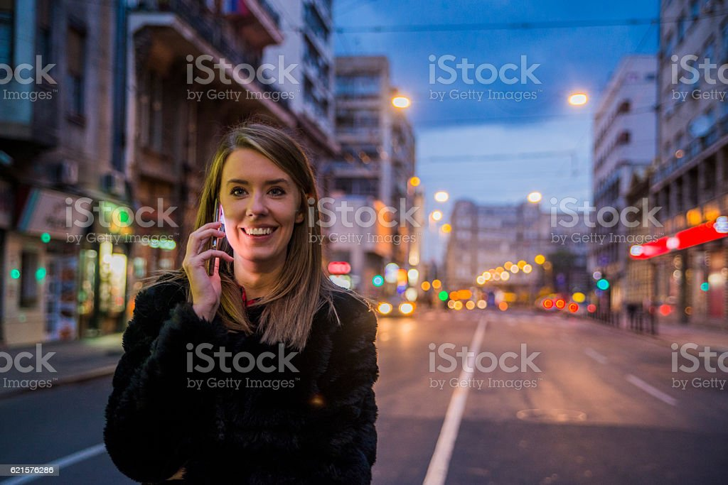 Beautiful girl talking with smart-phone, portrait in night city lights stock photo