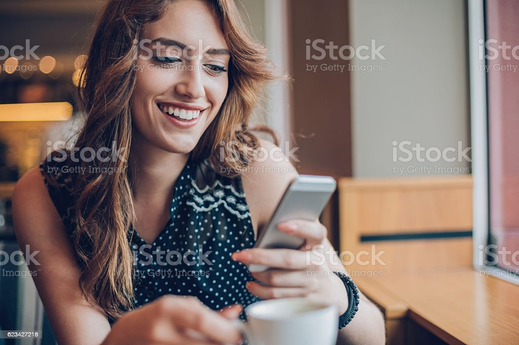 Beautiful girl texting in cafe stock photo
