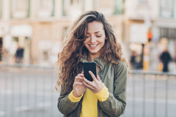 Beautiful girl texting on the street Young woman with smart phone texting outdoors in the city eastern europe stock pictures, royalty-free photos & images