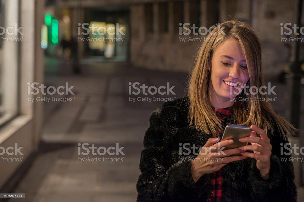 Beautiful girl texting with smart phone,night city lights stock photo