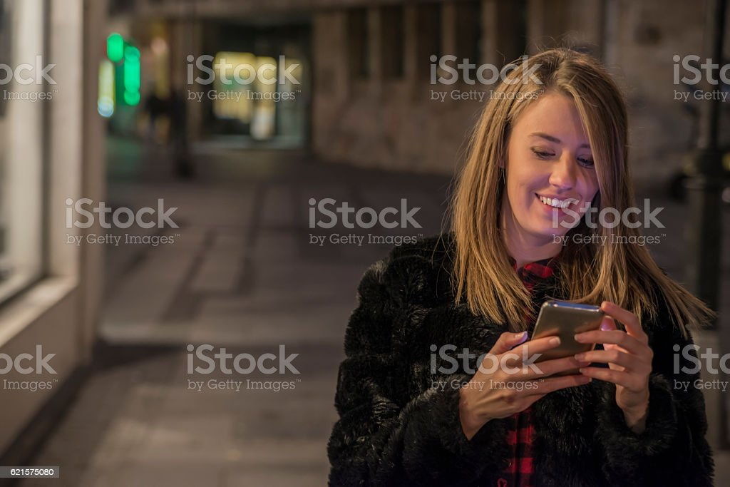 Beautiful girl texting with smart-phone, portrait in night city lights photo libre de droits