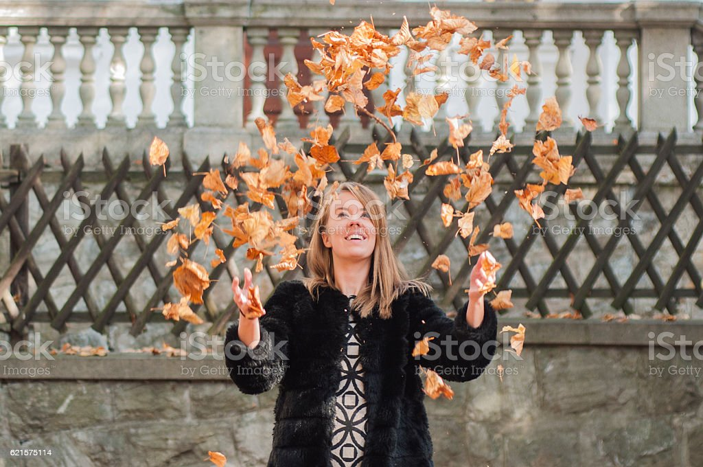 Beautiful girl throwing leaves in the air in autumn forest. photo libre de droits