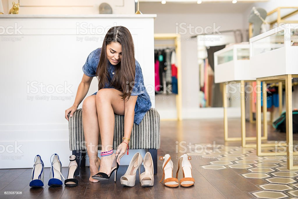 Beautiful girl trying on some shoes stock photo