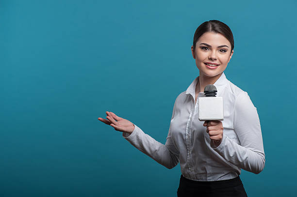Beautiful girl TV journalist with pretty smile is reporting Waist up portrait of elegant woman reporter with brown hair, who interviews and is smiling and looking at the camera holding the microphone and making a gesture with her right hand, isolated on a blue background and there is copy place in the left side anchor stock pictures, royalty-free photos & images