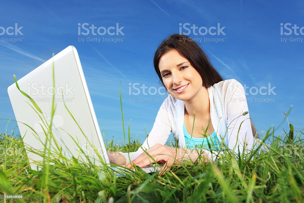 Beautiful girl typing on the laptop outdoor. royalty-free stock photo