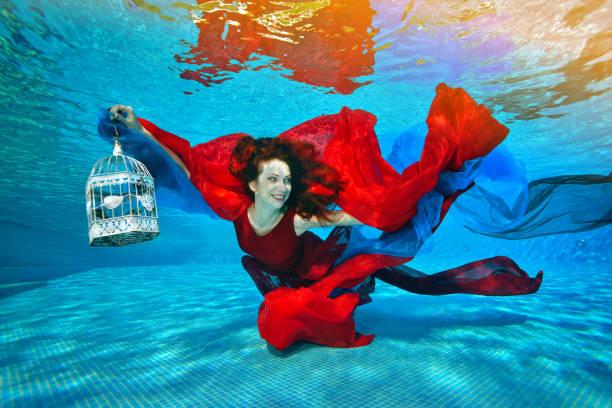 belle fille sous l'eau. elle nage et joue avec le tissu rouge et bleu sur le fond de la piscine. elle est titulaire d'une cage décorative dans sa main et les sourires. portrait. orientation paysage de l'image - défilé de mode photos et images de collection
