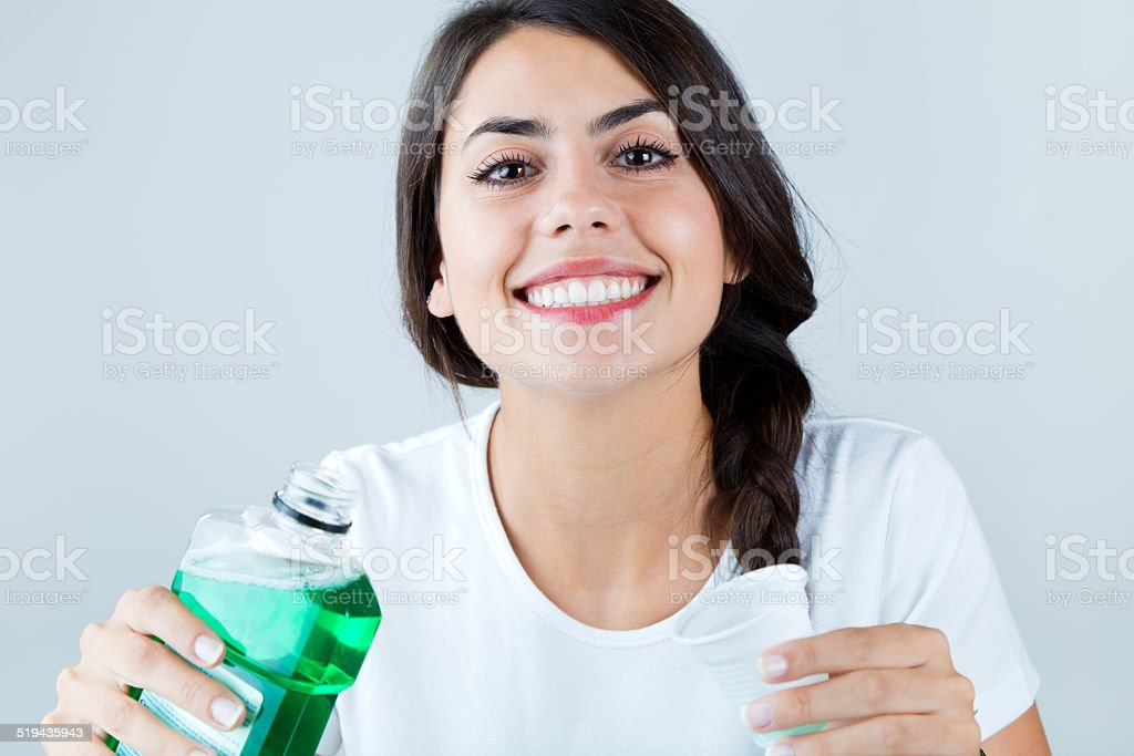 Beautiful girl using mouthwash. Isolated on white. stock photo