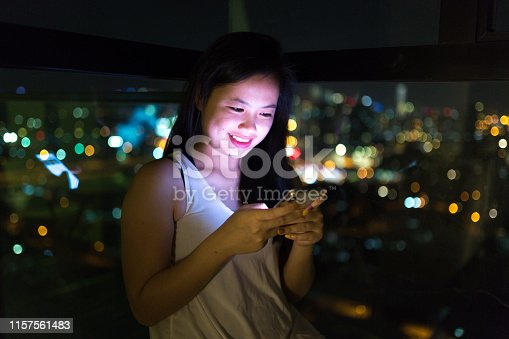Beautiful girl using phone in bedroom with city background