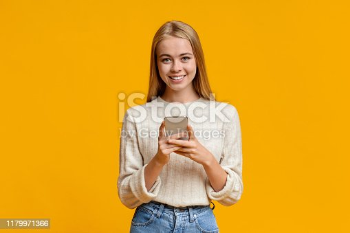 Cool Application. Cute teenage girl using smartphone on orange background, copy space