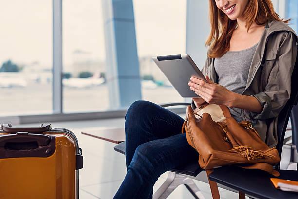 beautiful girl using tablet in airport - donna valigia solitudine foto e immagini stock