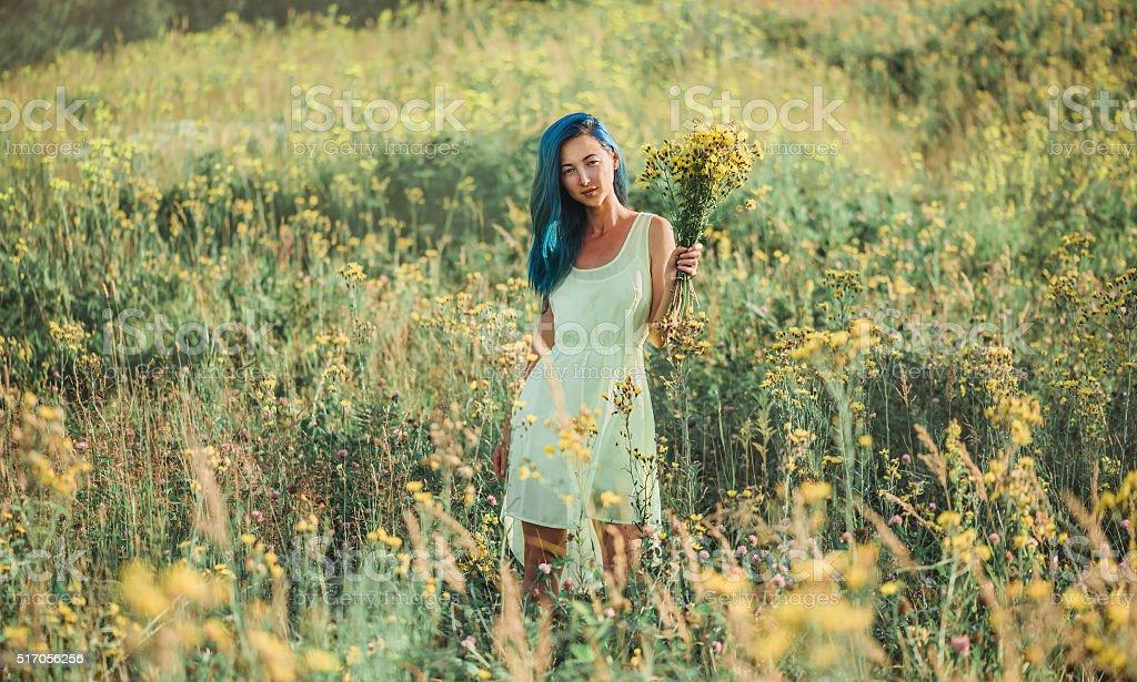 Beautiful girl walking on flower meadow stock photo
