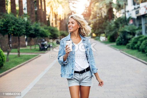 Beautiful girl walking on the street with cup of coffee