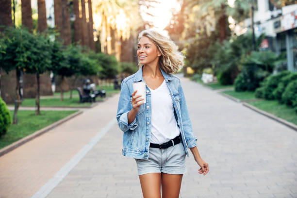 Beautiful girl walking on the street with cup of coffee Beautiful girl walking on the street with cup of coffee shorts stock pictures, royalty-free photos & images