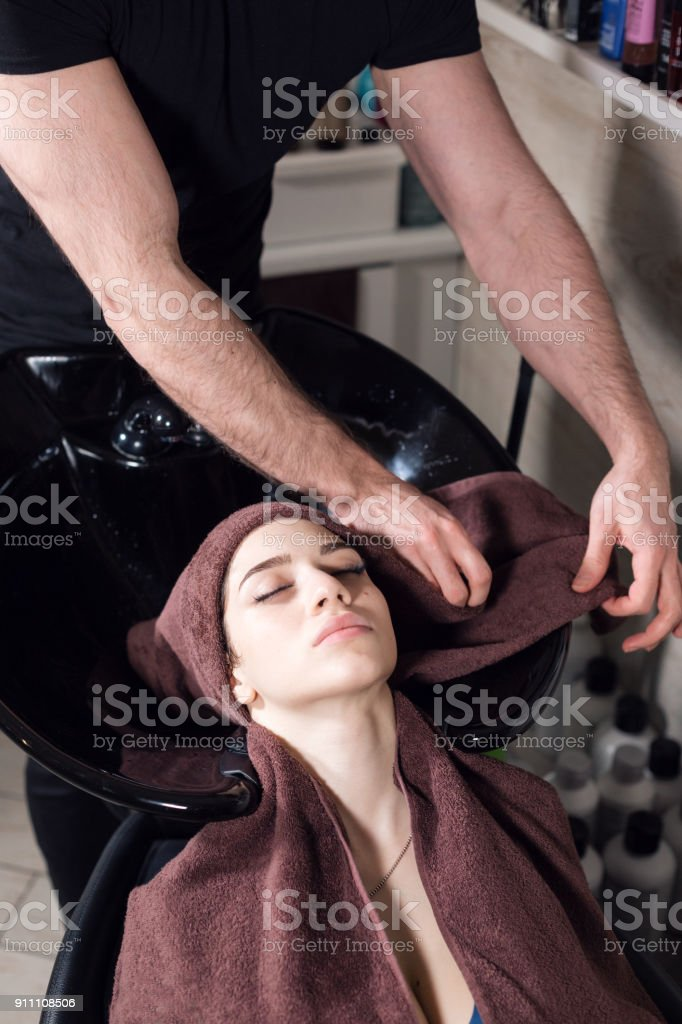 beautiful girl washes her hair before a haircut in a beauty salon. hair washing at a hairdressing, young caucasian girl. professional shampoo. stylist hairdresser man stock photo