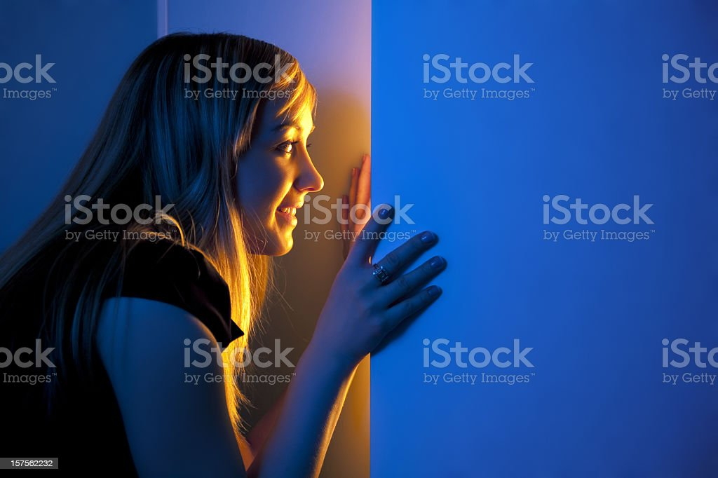Beautiful girl watching carefully behind the door stock photo