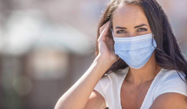 Beautiful girl wearing disposable facemask, looking into the camera during the coronavirus outbreak. stock photo