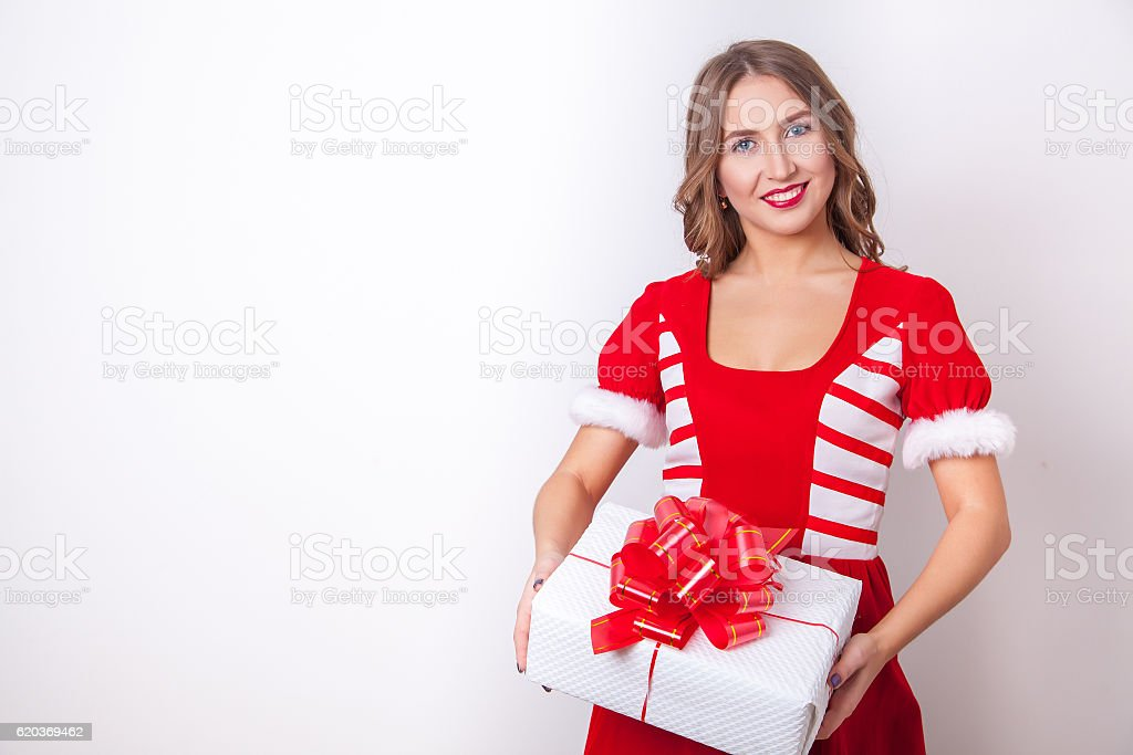 Beautiful girl wearing santa claus clothes with christmas gift zbiór zdjęć royalty-free