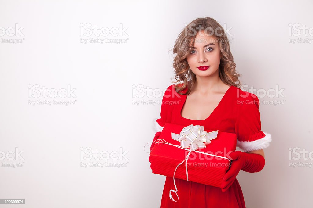 Beautiful girl wearing santa claus clothes with christmas gift zbiór zdjęć royalty-free