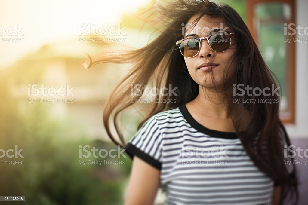 Beautiful girl wearing sunglasses enjoying fresh air in balcony. stock photo