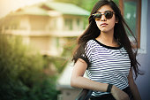 Outdoor image of beautiful, happy late teen urban girl enjoying fresh air in balcony at day time. She is wearing sunglasses, her long hair are flying in air. One person, horizontal composition with selective focus and copy space.