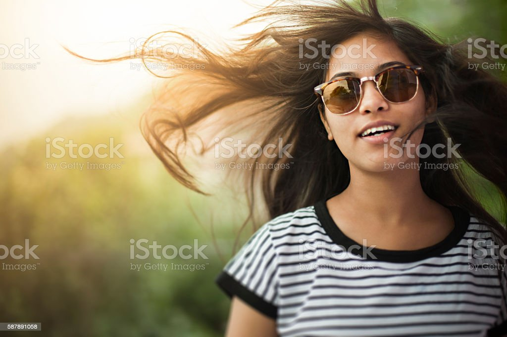 Beautiful girl wearing sunglasses with flying hair in nature. stock photo