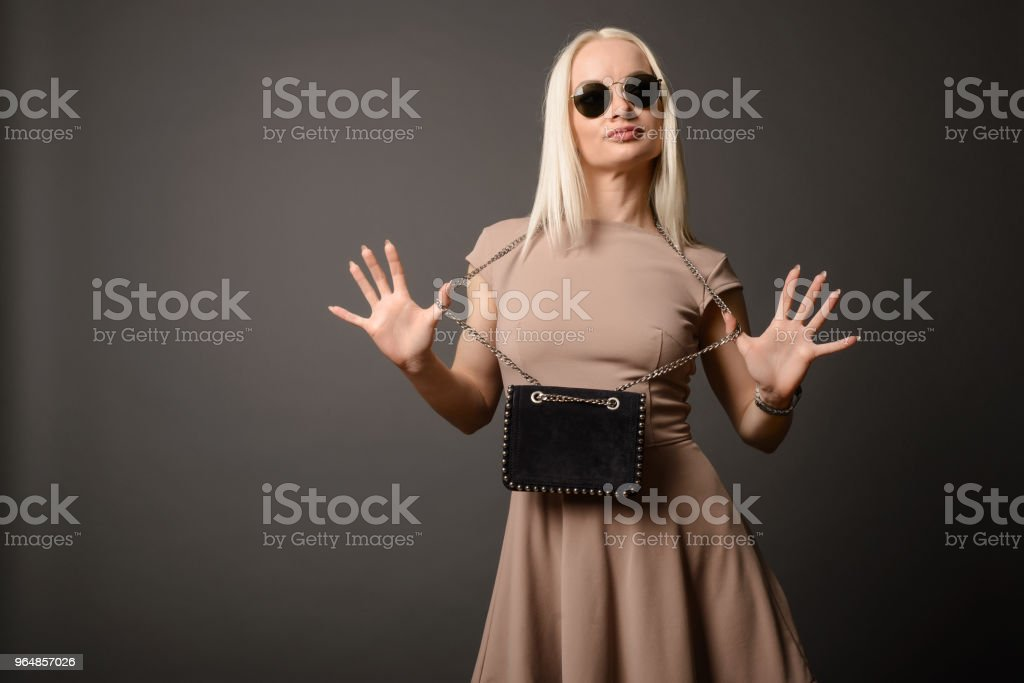 Beautiful girl with a handbag and sunglasses shows palms royalty-free stock photo