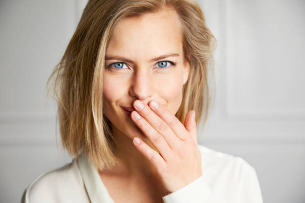 Beautiful girl with a secret Beautiful girl with hand over mouth, portrait embarrassment stock pictures, royalty-free photos & images