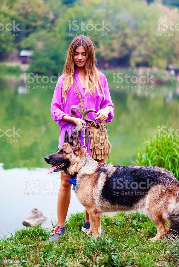Beautiful girl with a shepherd near the lake. stock photo