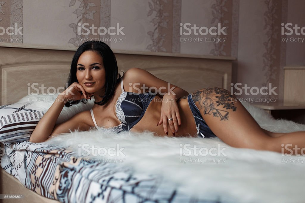 Beautiful girl with a tattoo  in lingerie lying stock photo