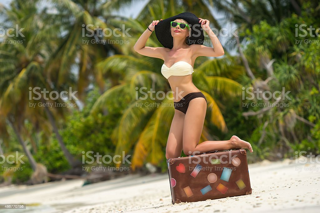 Beautiful girl with a vintage suitcase in a beach stock photo