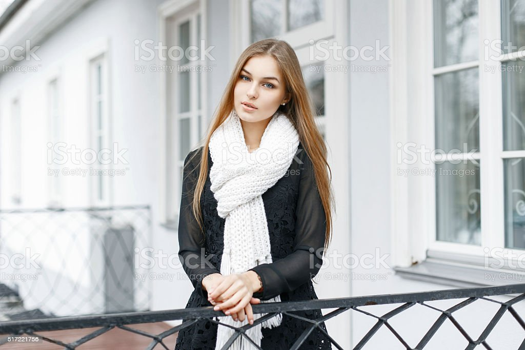 Beautiful girl with a white knitted scarf and a dress stock photo