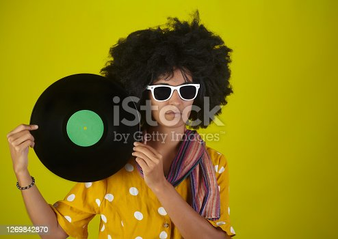 Beautiful girl with afro curly hairstyle and white eyeglasses holding an LP record on yellow background