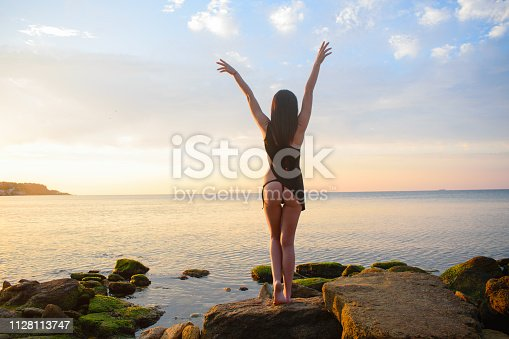 beautiful girl with an attractive body in a bikini against the sea and sunset, dawn
