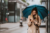 istock Beautiful girl with an umbrella standing in the rain typing a message. 1316269619
