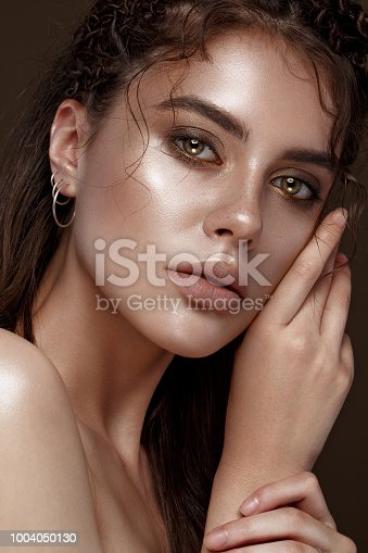 Beautiful girl with an unusual hairstyle and creative makeup. Beauty face. Photo taken in the studio.