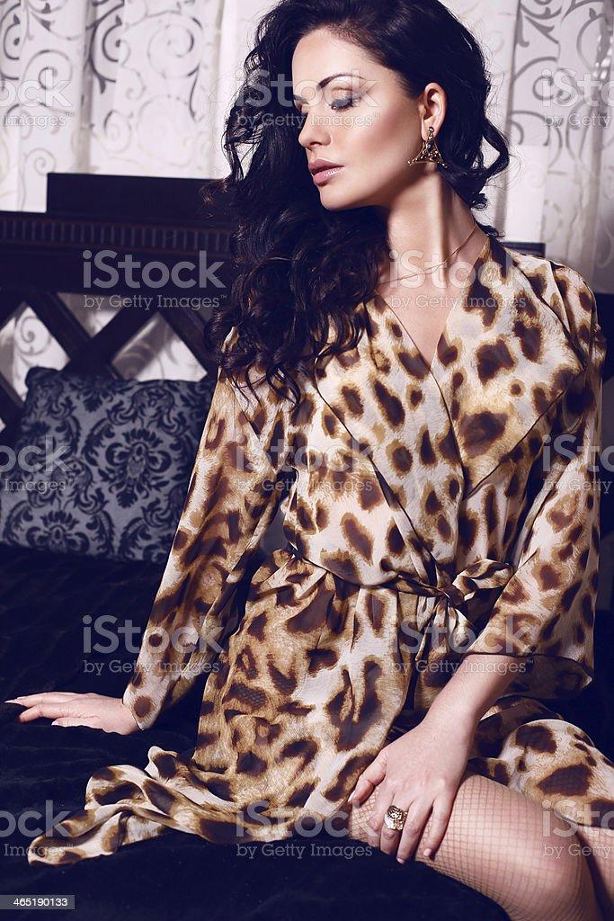 beautiful girl with black hair sitting on divan stock photo