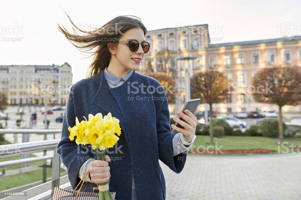Beautiful girl with bouquet of yellow spring flowers, young woman reading text with smartphone, background city architecture, golden hour royalty-free stock photo
