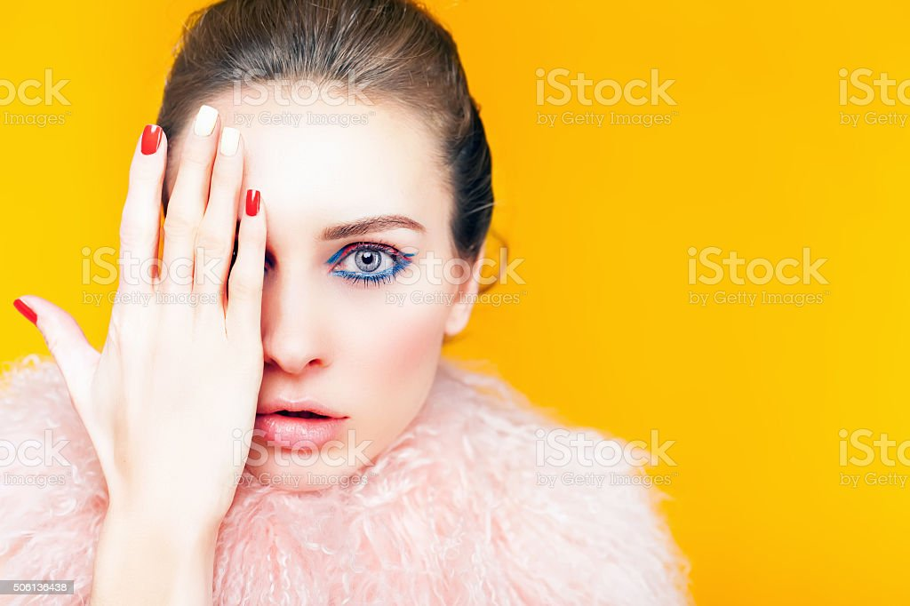 Beautiful girl with bright makeup dressed in luxury fur coat stock photo