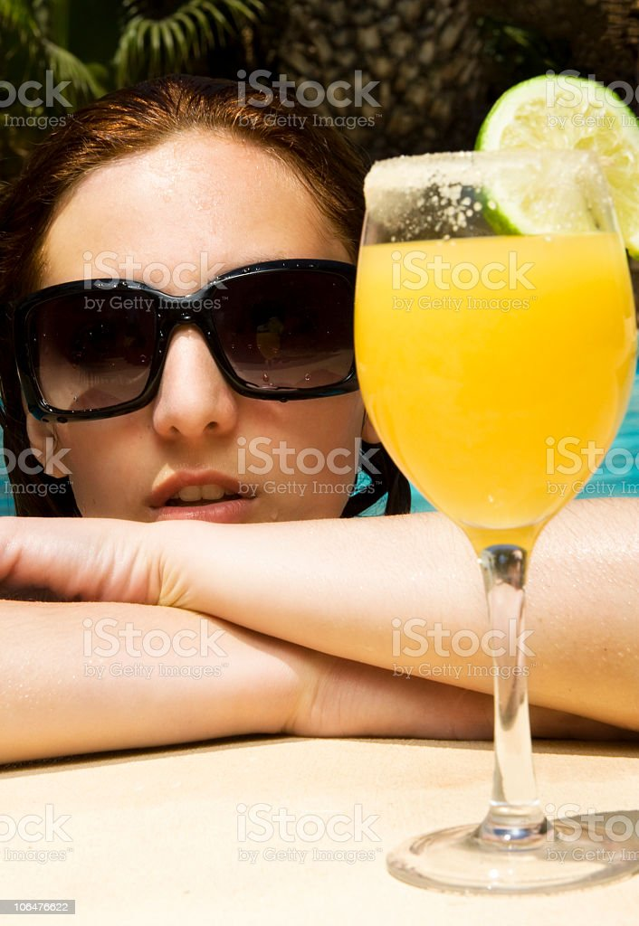 Beautiful girl with cocktail in the pool royalty-free stock photo