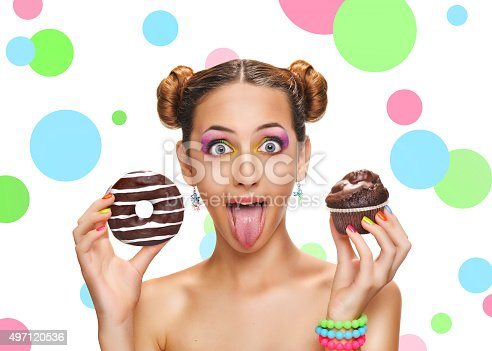 692840848istockphoto Beautiful girl with colorful donut and muffin . 497120536