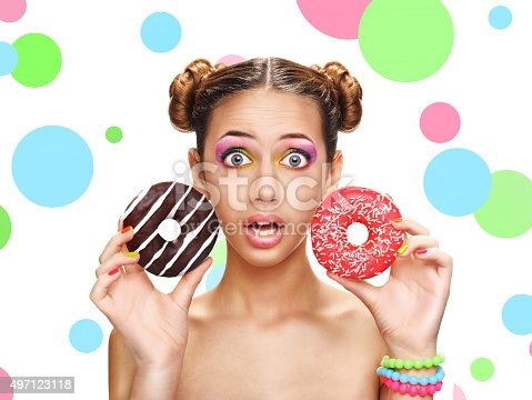 692840848istockphoto Beautiful girl with colorful donuts. 497123118