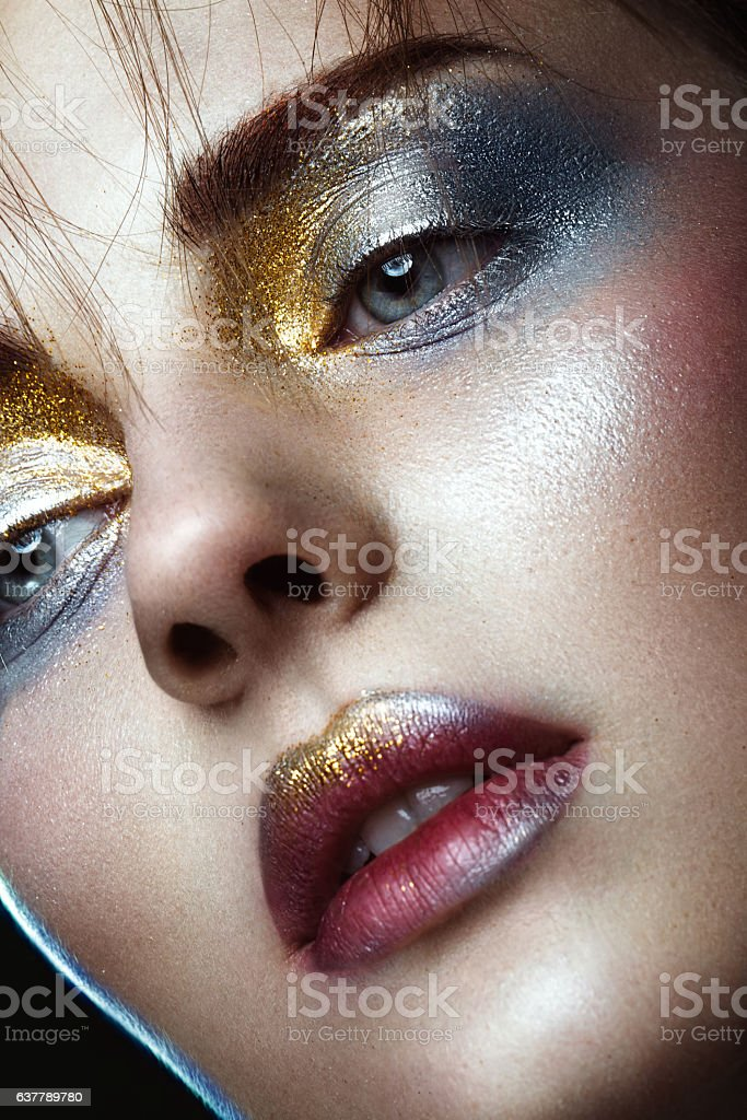 Beautiful girl with creative golden and silver glitter make-up stock photo
