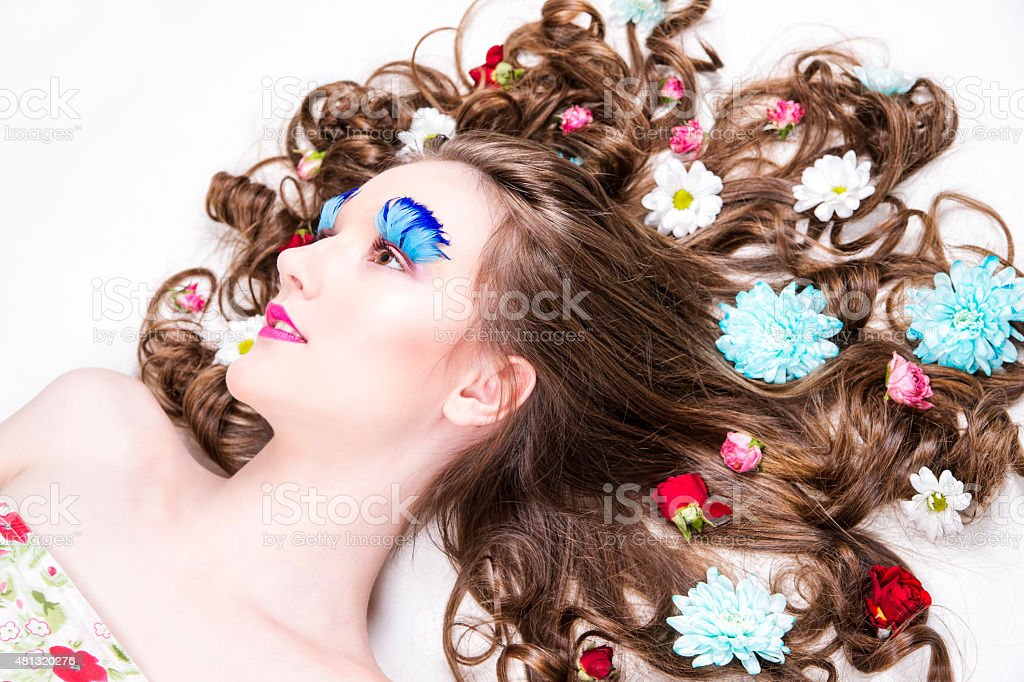 Beautiful girl with creative make-up and hairstyle with flowers stock photo