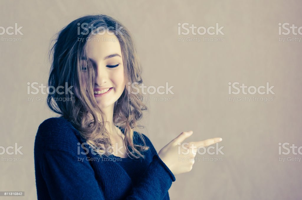 Beautiful Girl With Curly Hair Pointing To The Side Stock Photo